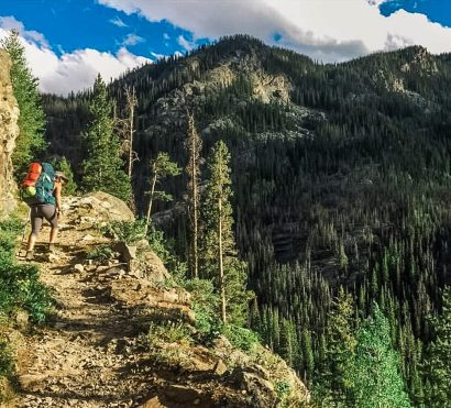 Hiker climbs cliff trail in Rocky Mountain National Park