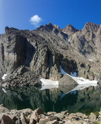 Snowy mountains next to reflective lake on Longs Peak hike