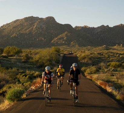 Bike group rides desert road on road cycling trip