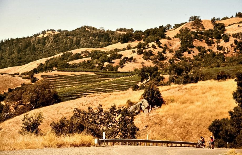 Cyclists walk their bikes in front of Sonoma hills