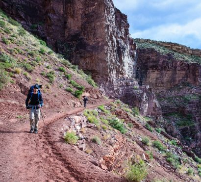 Hikers navigate cliffside trail on Grand Canyon backpacking trip