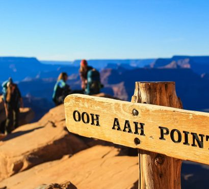 Hiking group looks over Grand Canyon behind Ooh Aah Point sign