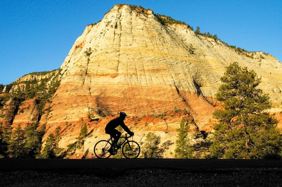 Silhouetted cyclist against southern Utah cliff at sunset
