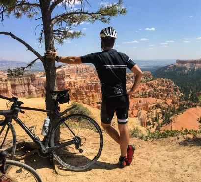 Cyclist leans against tree to view southern Utah canyon
