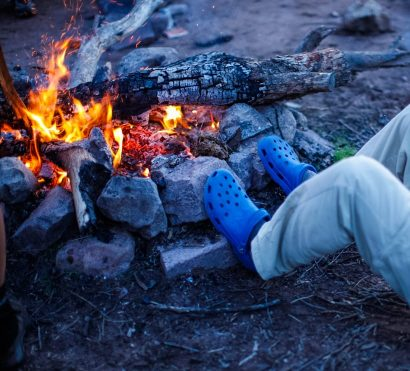 Hiker rests feet against campfire on Superstition Mountains trip