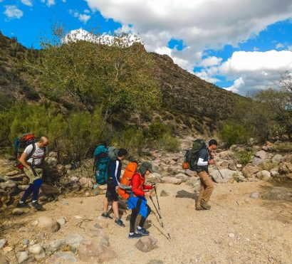 Tour group hikes Superstition Mountains wilderness