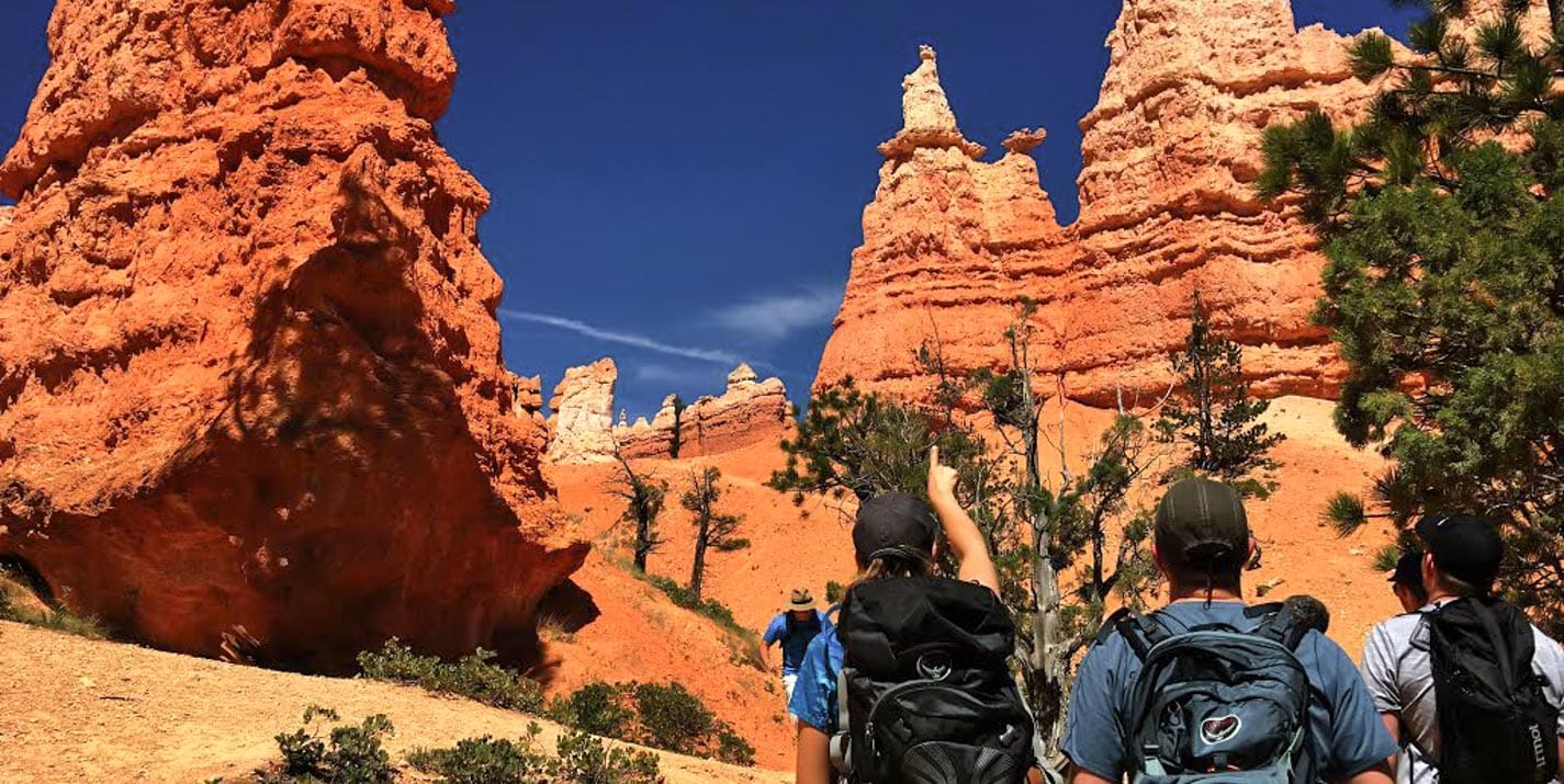 Hiking tour group points at rock formation in Bryce Canyon.