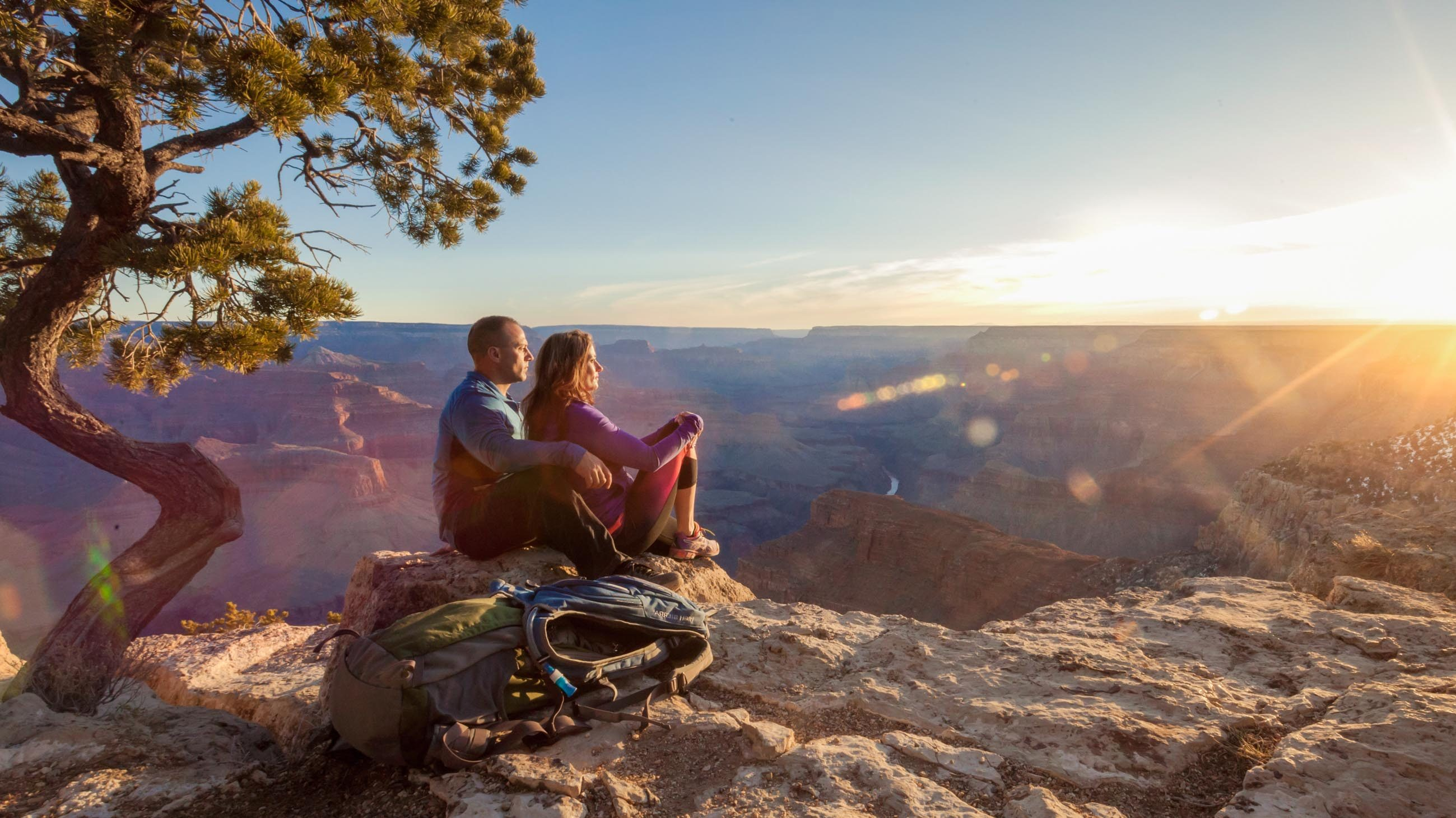 Hikers sit on rocky overlook to watch Grand Canyon sunset