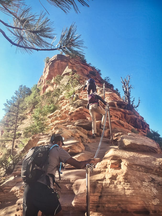 Hiking group uses railing to climb rock formation on Zion trip