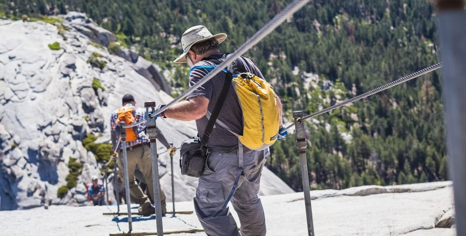 Hikers use cable railing to descend Yosemite Half Dome trail