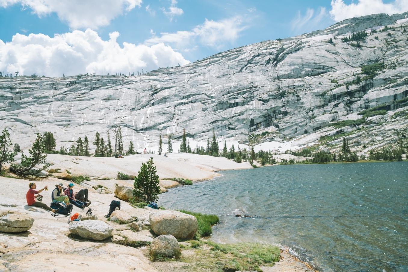 Backpacking tour group rests beside Yosemite lake