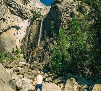 Hiker looks up at Yosemite Falls in Yosemite National park