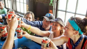 A group of people make a toast with tecate.
