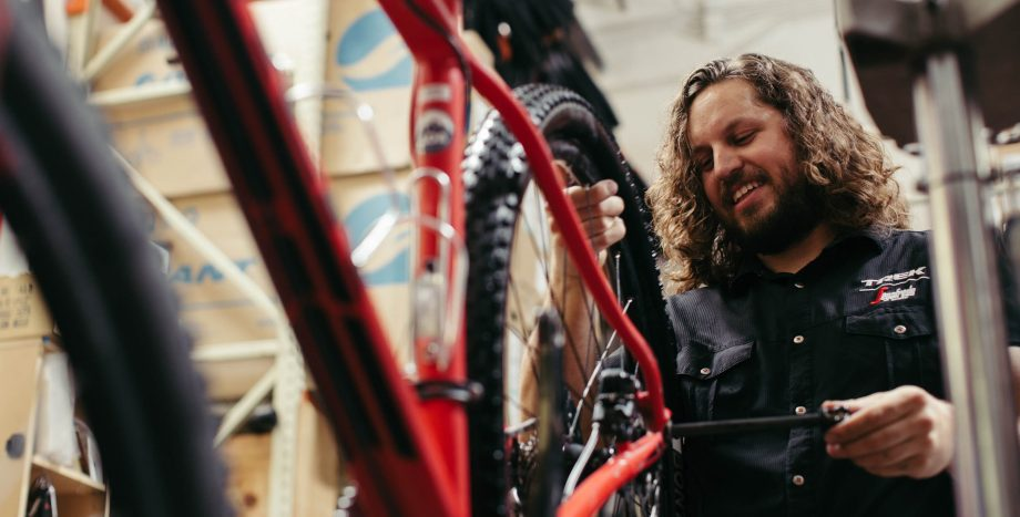 Smiling mechanic repairs bike at Scottsdale rental shop