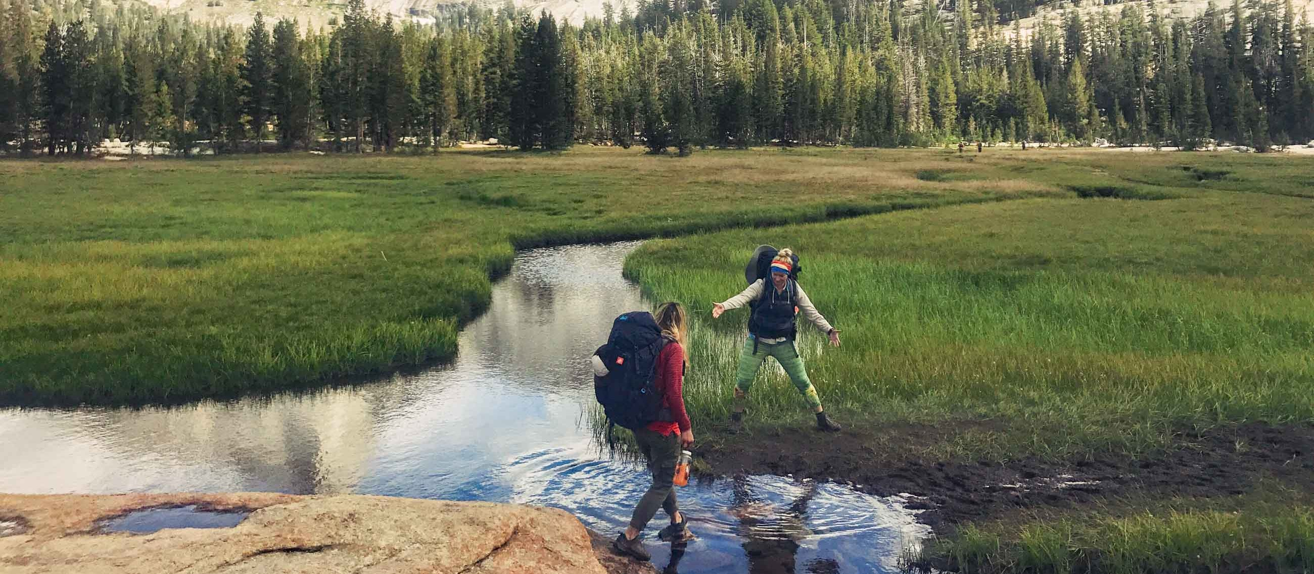 Hikers help each other across field stream at Yosemite.
