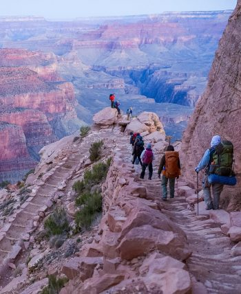 Hikers overlook Colorado River in Grand Canyon at sunset.