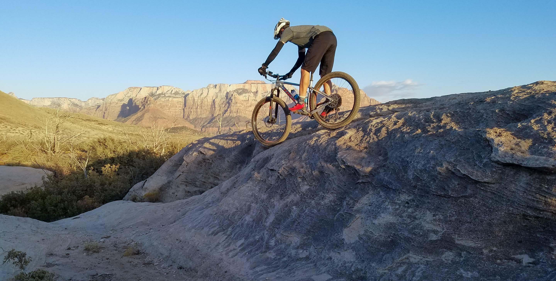 Mountain biker descends rocks on Gooseberry Mesa trail tour