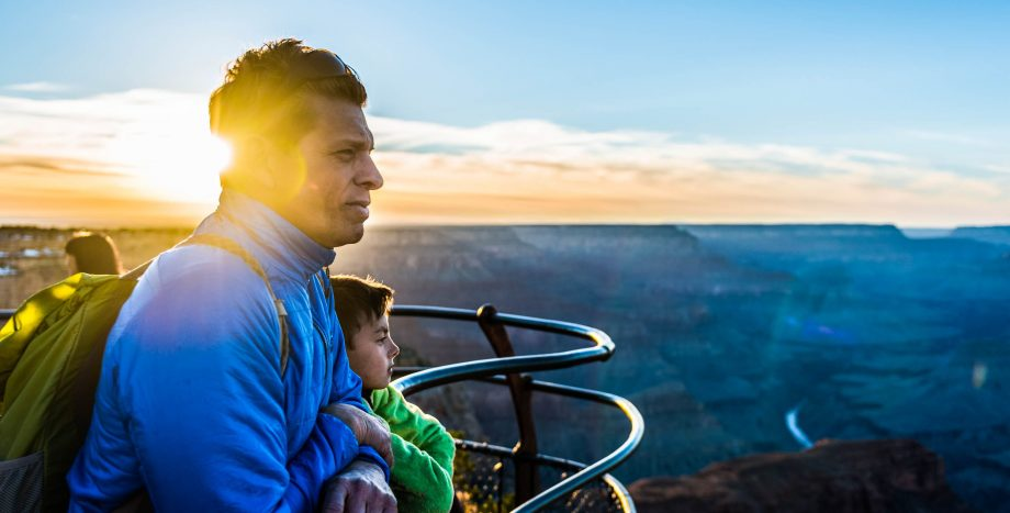 Man and child overlook Grand Canyon at sunrise