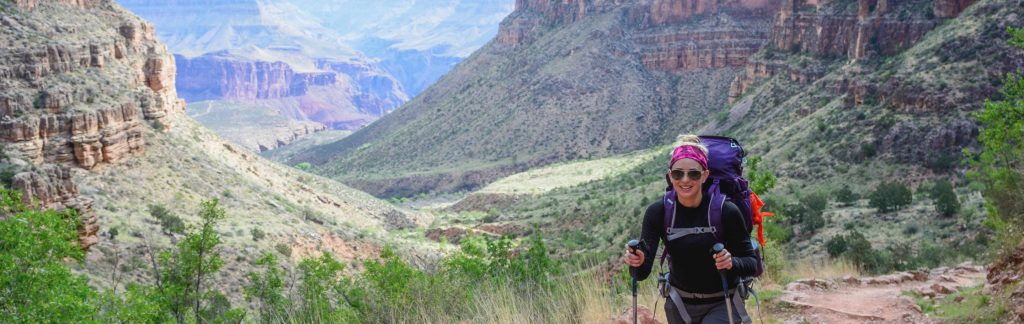 Smiling hiker approaches camera on Grand Canyon trail.