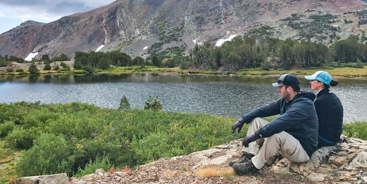 Hikers sit next to pond on Mono Pass Trail at Yosemite.