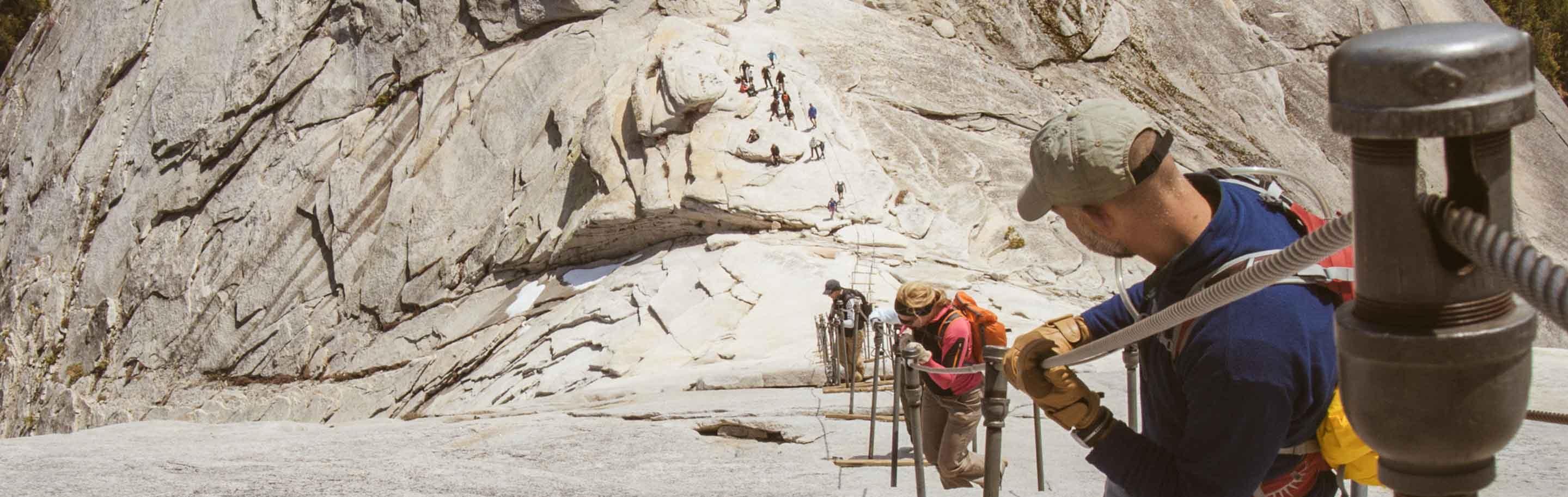 Hikers use cable railing to navigate Yosemite ridge trail.