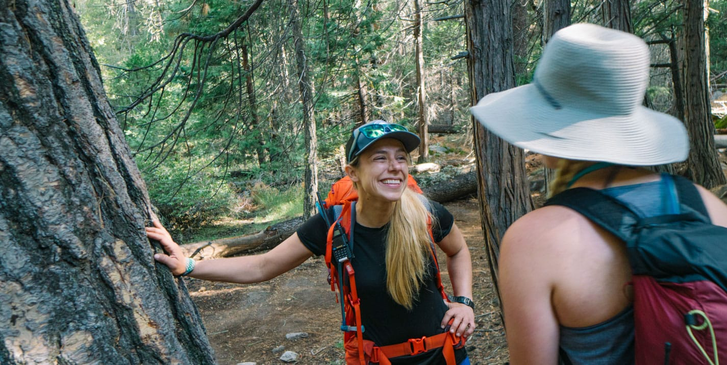 Smiling Yosemite National Park tour guide in forest.