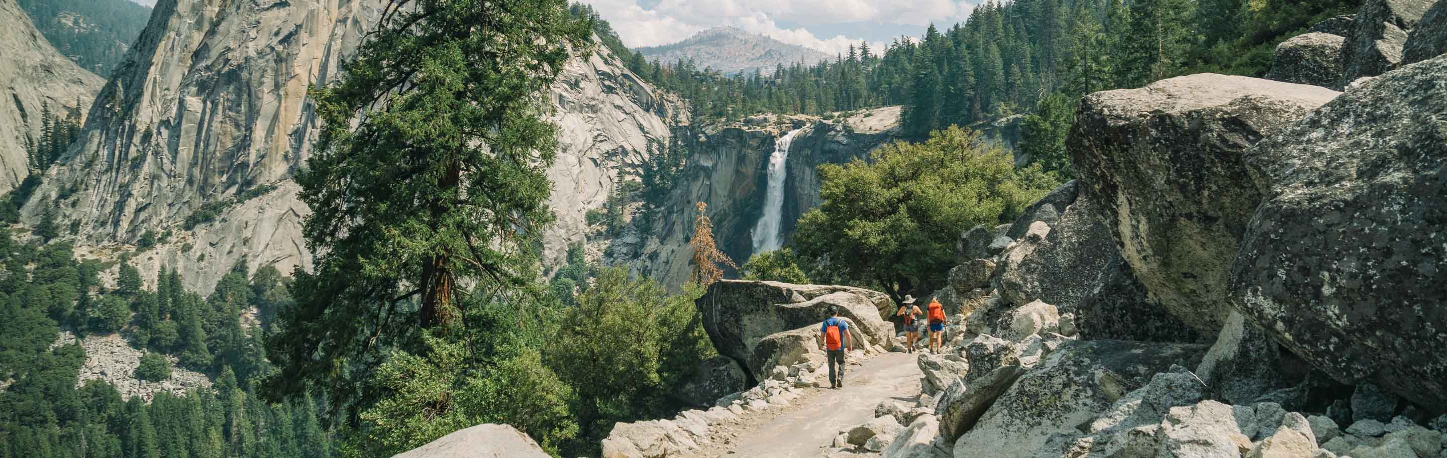 Hiking group climbs rocky trail toward Yosemite waterfall