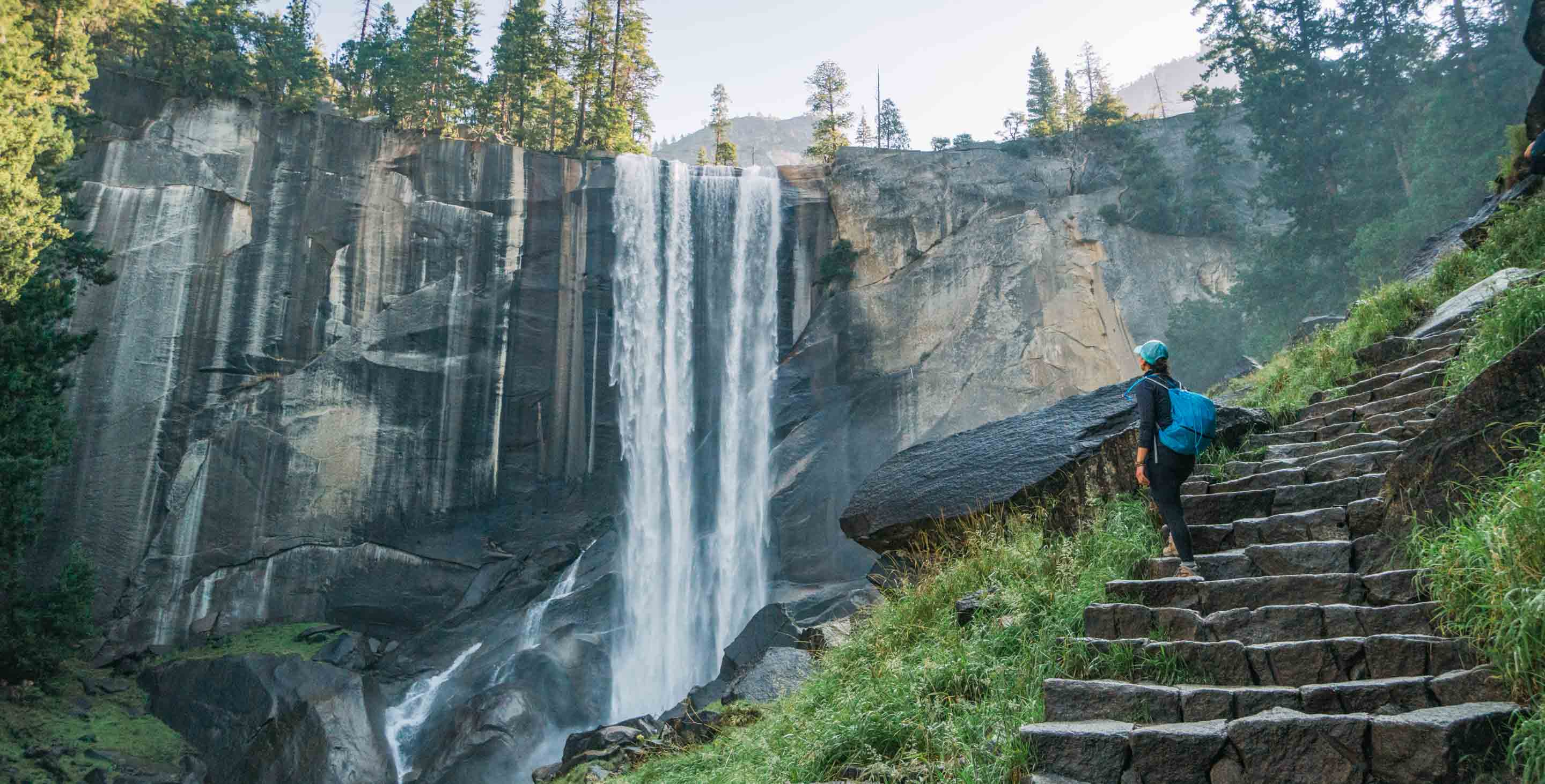 Hiker pauses on stone steps to view Yosemite waterfall.