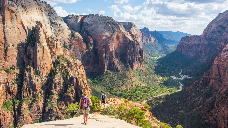 Hikers descend rocks into Zion National Park canyon