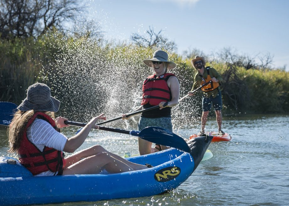 Paddlers on the water laughing and splashing one another