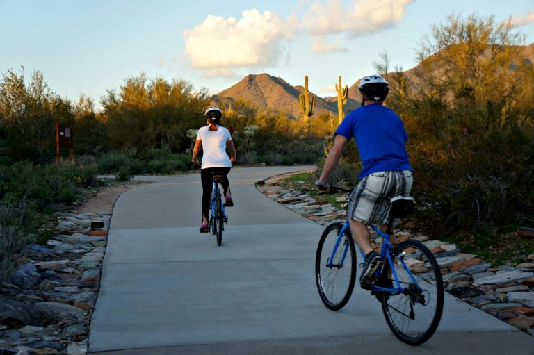 Two people riding bikes down a sidewalk.