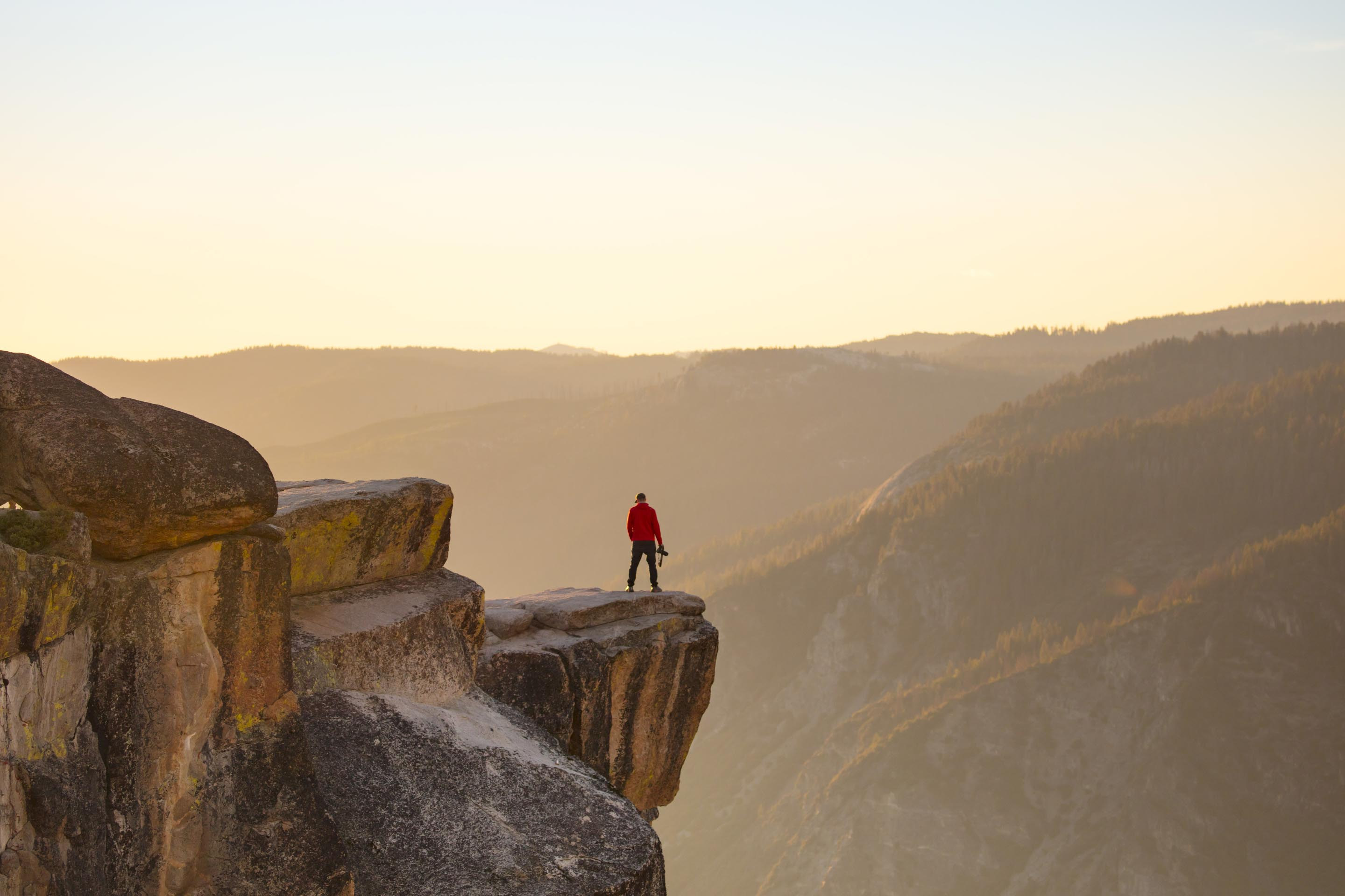 Hiker standing on the edge of Taft Point in Yosemite National Park