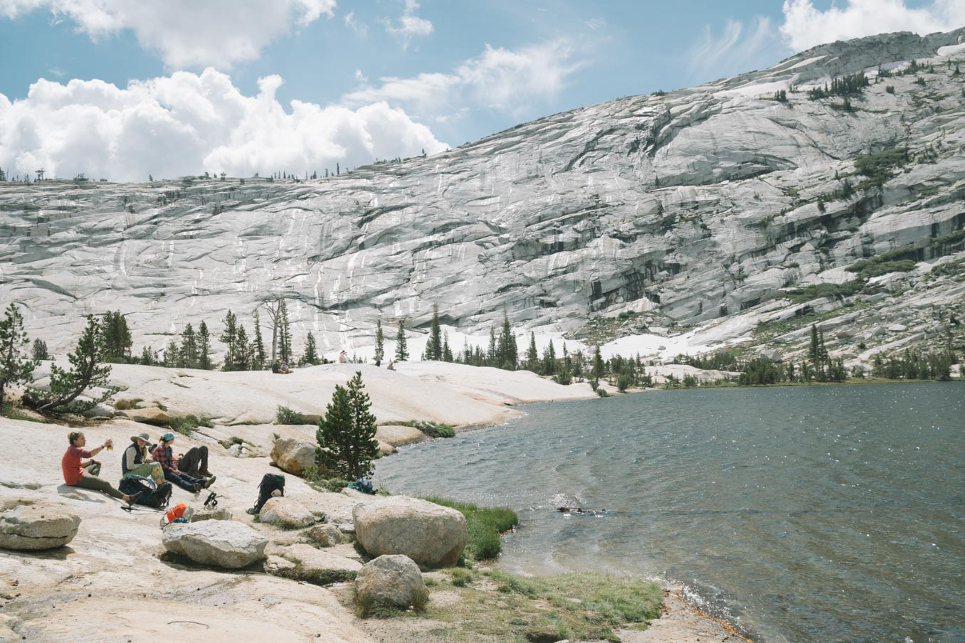 Hikers enjoy a rest sitting on a lake next to a mountain.