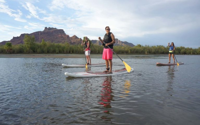 three people paddleboard on the salt river in front of red mountain