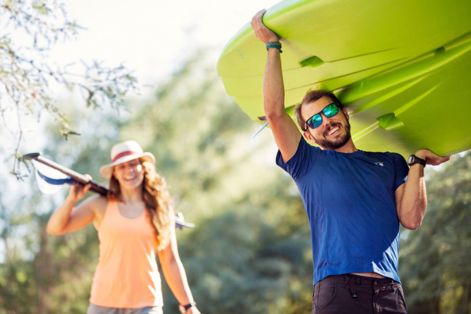 Man carrying green stand up paddle board on shoulder
