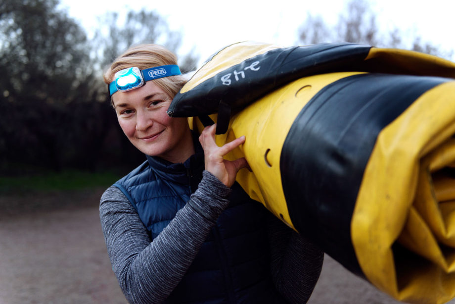 woman carrying rolled up yellow kayak on shoulder