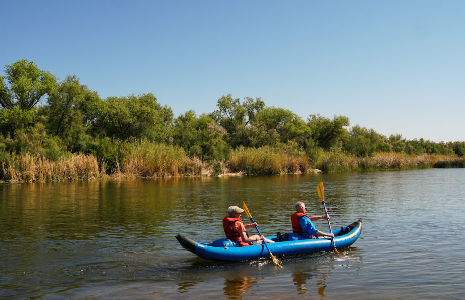 two people in an inflatable kayak with a river and plants