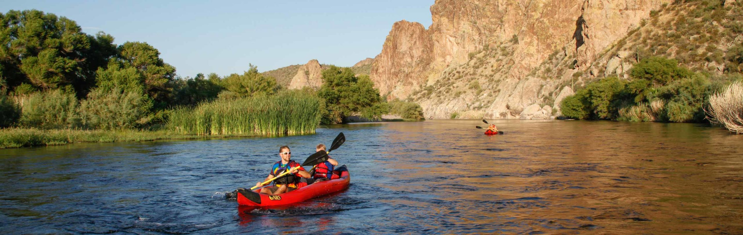 Kayakers in inflatable kayaks on the lower Salt River in Arizona