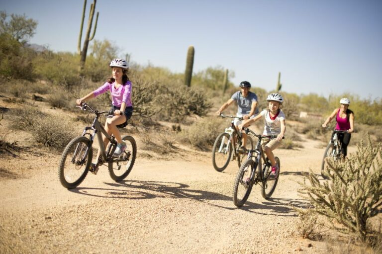 family mountain biking through saguaro cactus