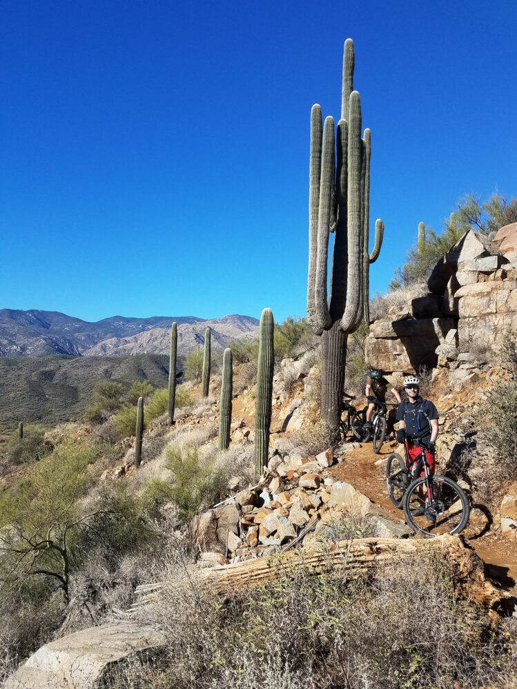 Mountain biker stands beside their bike before the Black Canyon Trail