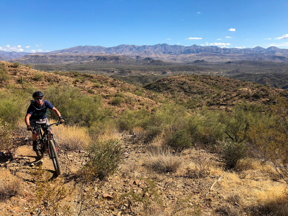 mountain biker riding towards you with desert mountains in background