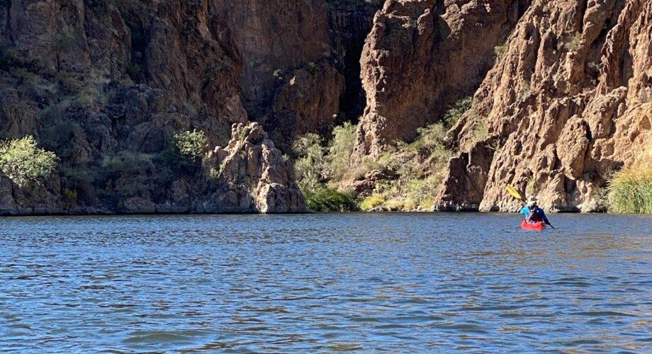 person in red kayak paddling towards rocks