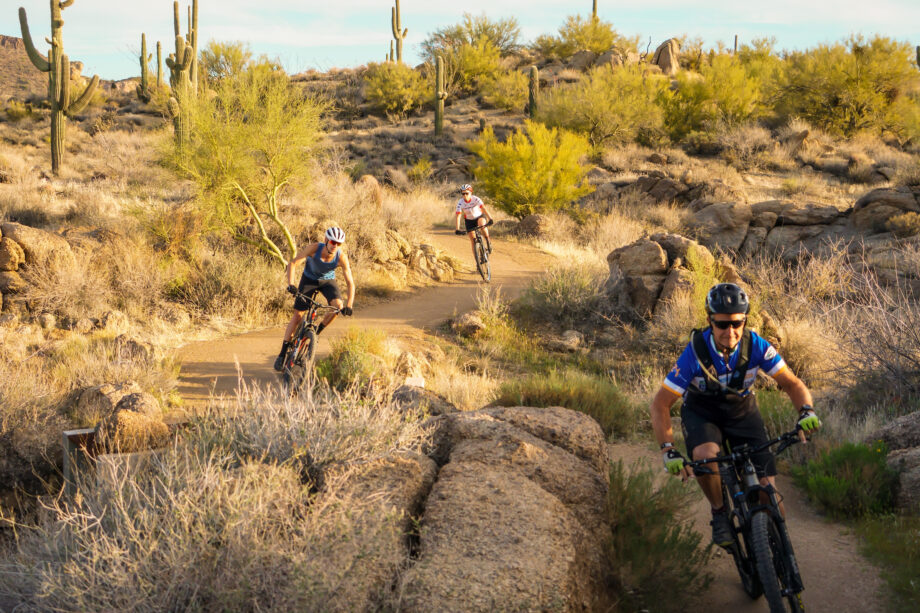 three mountain bikers ride in a line toward the camera around windy desert trail