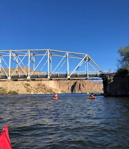 two kayakers paddle underneath a bridge at Canyon Lake in Arizona