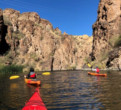 two kayakers in orange kayaks face a canyon wall at Canyon Lake in Arizona