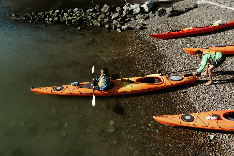 A single person in a tandem kayak prepares to launch their boat as part of Point Reyes kayak tour